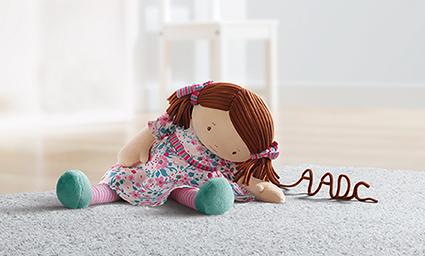 Puppenmädchen, dessen Haar zu einem Schriftzug werden: AADC