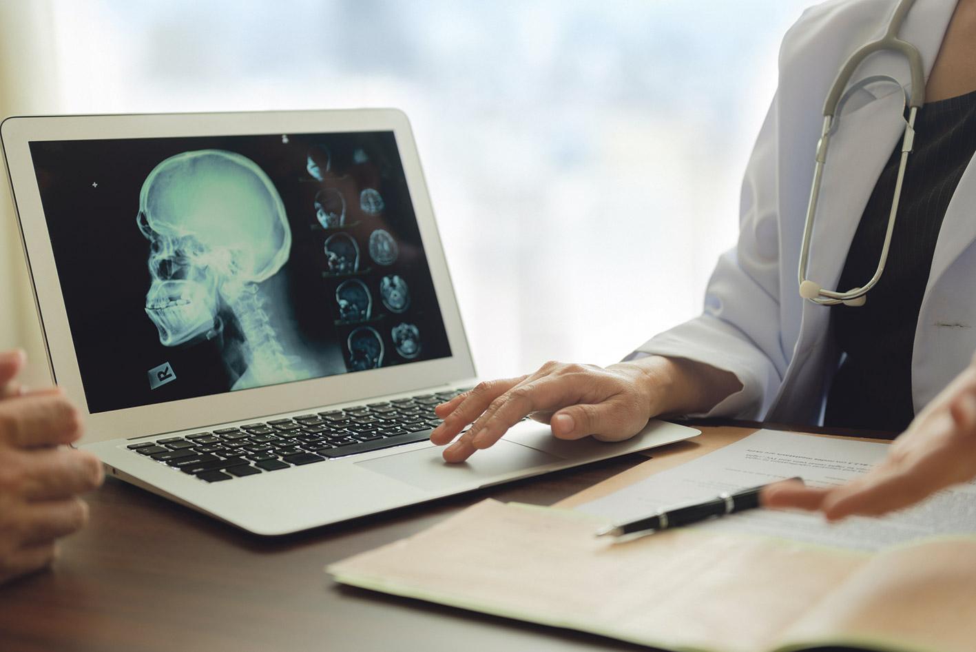 Ärztin, die am Schreibtisch sitzt und ein Schädel-MRT zeigt.