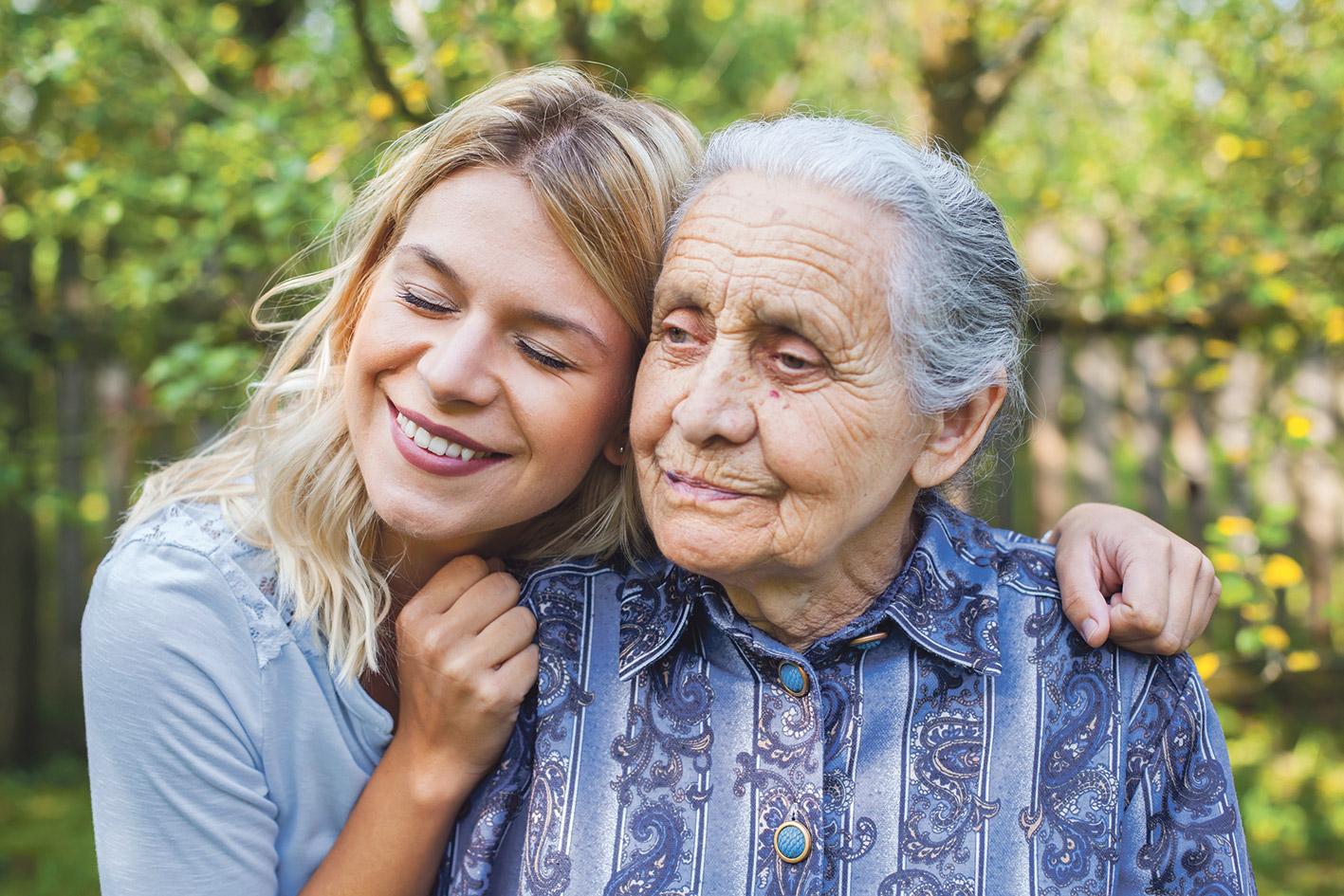 Enkelin umarmt ihre demente Großmutter.