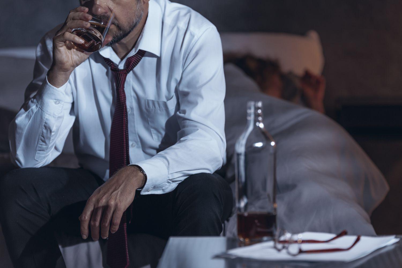 Ein Mann sitzt auf seinem Bett und trinkt, vor ihm eine Flasche mit Alkohol. Thema: Suchtverhalten