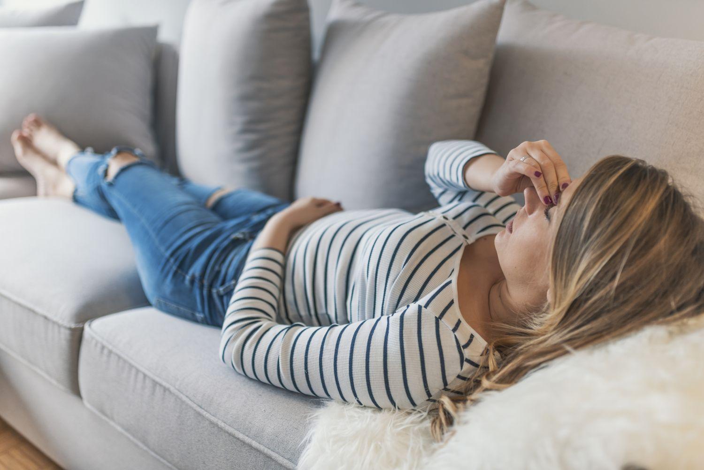 Frau liegt mit Migräne auf dem Sofa