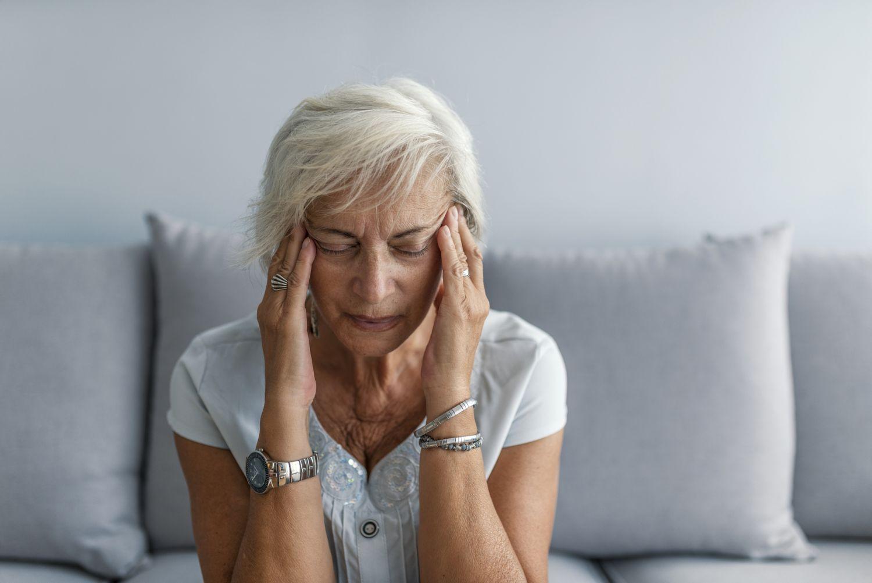 Ältere Frau fässt sich an die Schläfen. Sie hat vermutlich einen Migräneanfall.