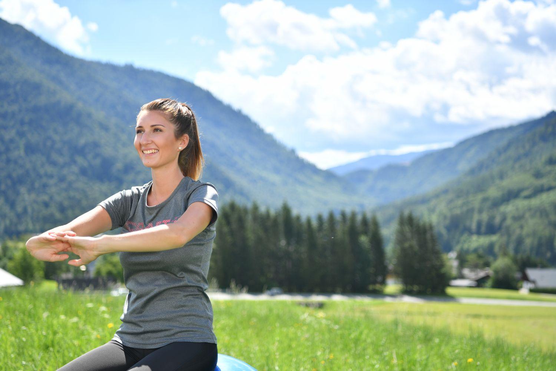 Frau sitzt vor einer idyllischen Berglandschaft.