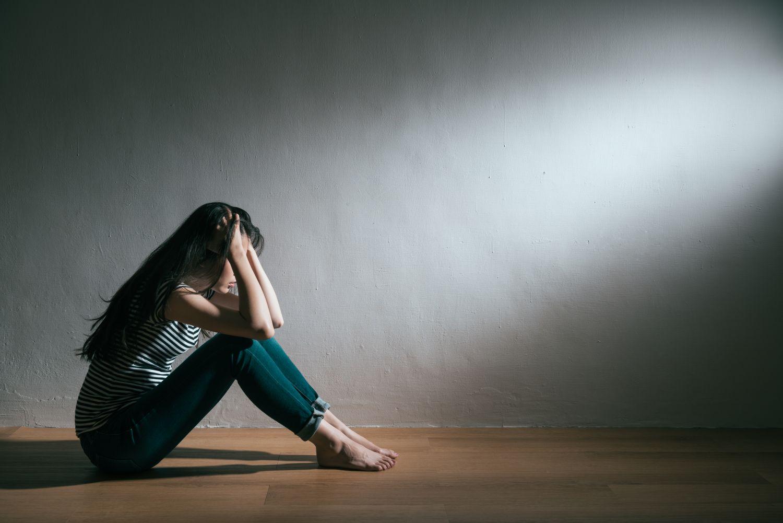Verzweifelte Frau sitzt auf dem Boden und rauft sich die Haare. Thema: Transkranielle Magnetstimulation bei Depression