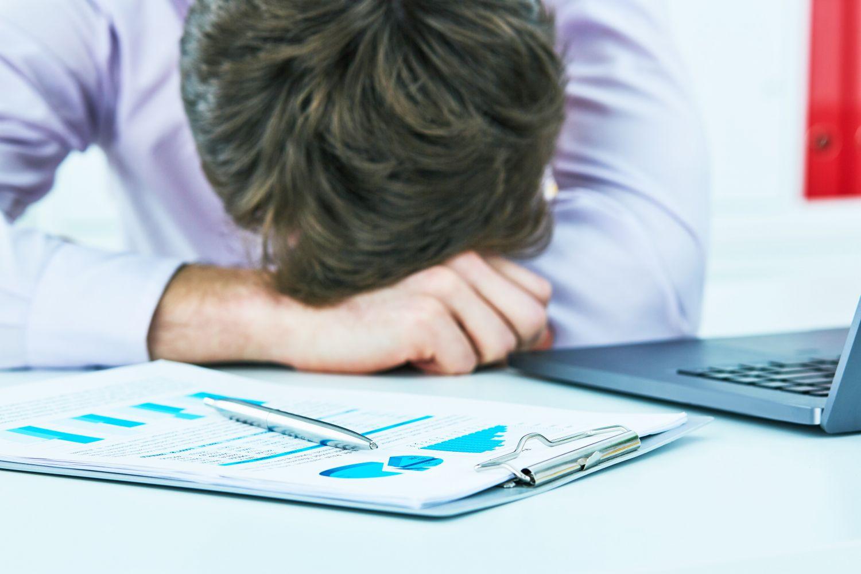 Mann schlafend am Schreibtisch; Thema: Schlafkrankheit