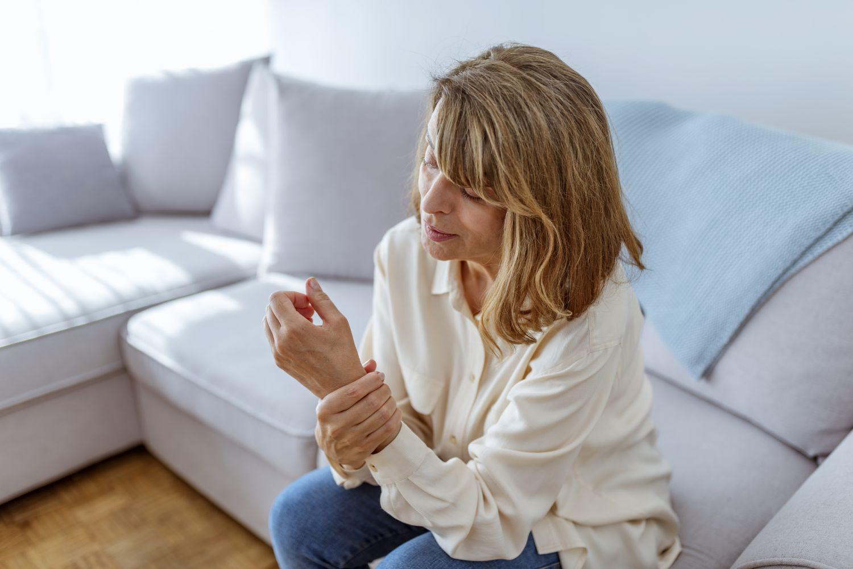 Frau, die sich das Handgelenk hält. Thema: MS-induzierte Spastik