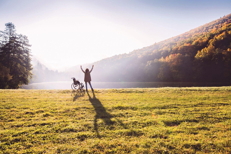 Person, die neben einem Rollstuhl steht vor einer See-Berg-Wald-Landschaft.