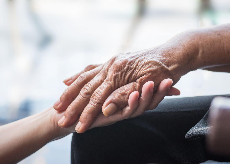 Eine junge Hand hält eine ältere Hand. Thema: Parkinson erkennen